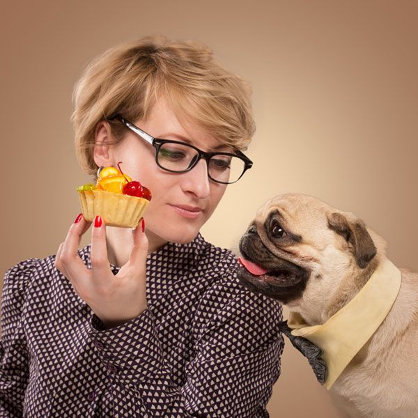 Don't ask your dog if she wants a cupcake. Of course she wants a cupcake. Woman stopping her dog from eating cake by Shutterstock.