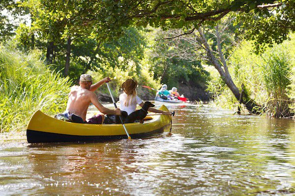 (Couple canoeing with their dog by Shutterstock)