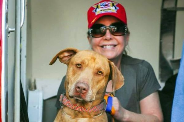 Pilot Cindy Smith poses with one of the dogs saved from a Los Angeles county shelter. Photo credit Ric Browde.