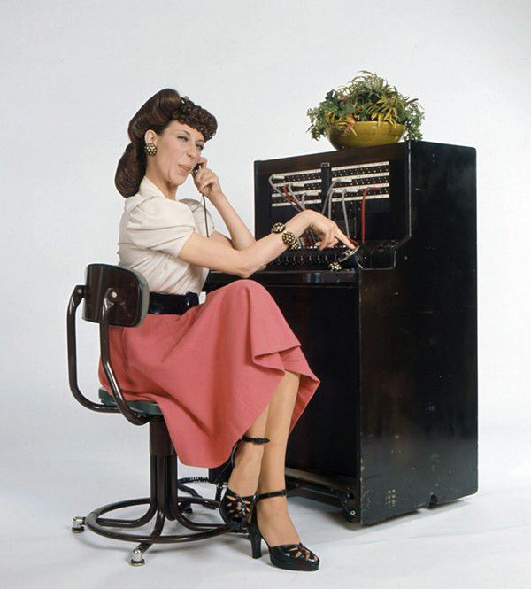 lily tomlin sitting at a switchboard in the persona of Ernestine the operator.