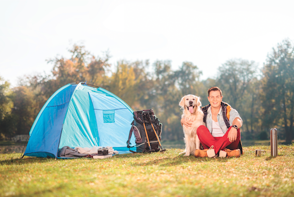 Man and dog camping by Shutterstock.