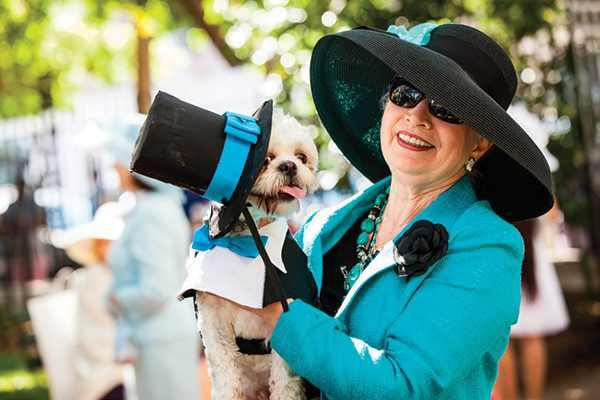 A dog and a woman dressed up in fancy hats.