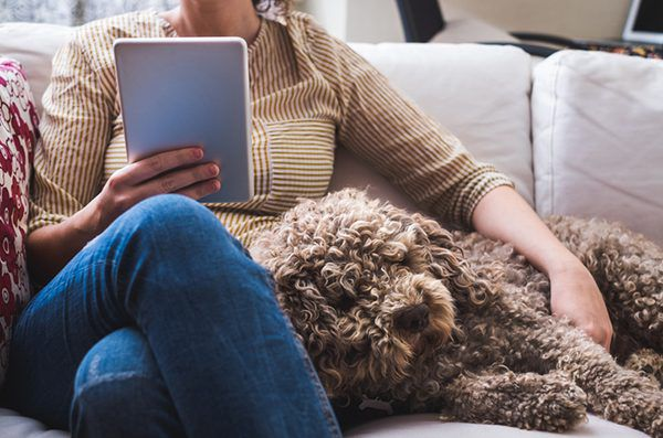 A woman on a couch with her dog. Photography by ballero/Thinkstock.