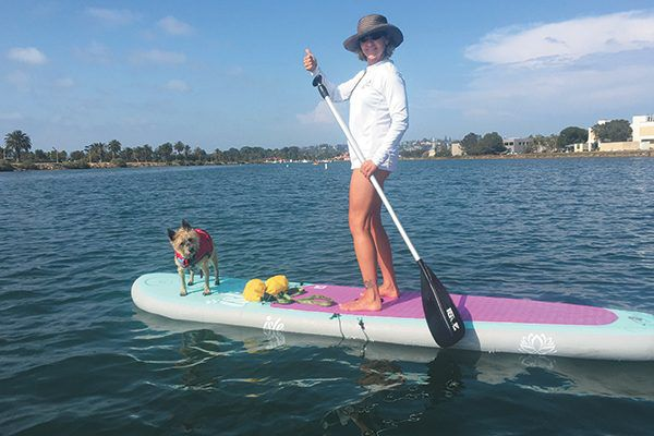 A woman stand up paddleboarding with her dog.