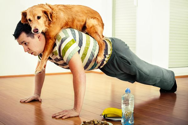 A man doing pushups exercises with his dog.