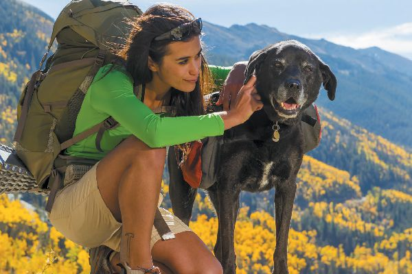A woman hiking with her dog.