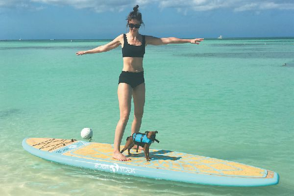Sigrid and Sprout try their hand/paw at paddleboarding, one of the many outdoor activities available.