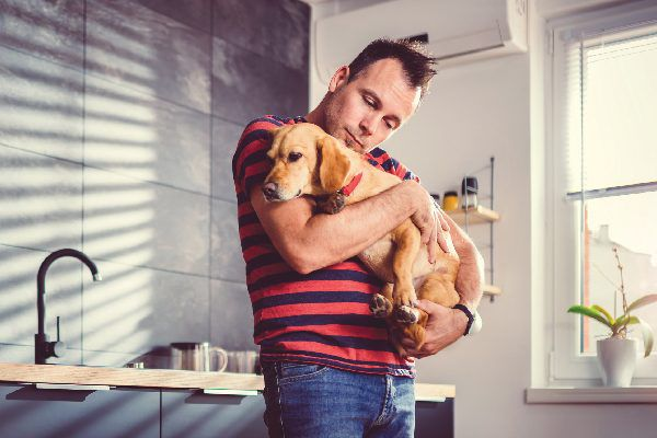 A man holding a dog in an apartment kitchen.