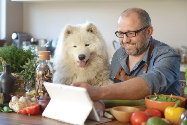 A man cooking with his dog.