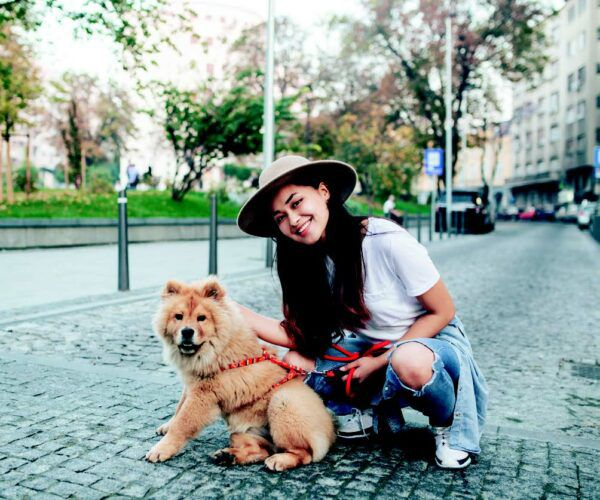 a woman sitting with her dog on gray a brick-lined road. learn how to help your fearful dog.